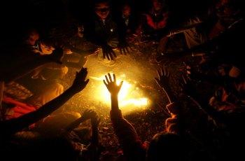 """""""Buscando calor"""". Nenos quentándose ao lume en Bhubaneswar, India. Observador Global.com"""